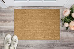 Blank coir doormat before the door in the hall. Mat on wooden floor, flowers and shoes. Welcome home, product Mockup.  stock illustration