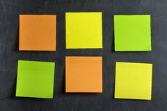 Blank Colored Postits Post-its Blackboard. Blank Green orange and yellow postits or post-its glued on dirty blackboard or chalkboard. Please visit my personal Stock Photography