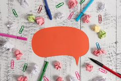 Blank colored speech bubble pens ballpoints clips binders crushed paper balls lying retro vintage rustic old table royalty free stock image