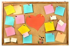 Blank colorful paper notes , office supplies and red paper heart on cork message board. Editable blank paper notes and office supplies (paper clips, pins Stock Photo