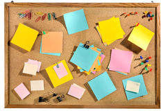 Blank colorful post it notes and office supplies on cork message board. Editable blank paper notes and office supplies (paper clips, pins, thumbtacks) on cork Royalty Free Stock Photography