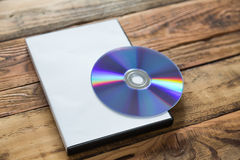 Blank compact disc with cover on wood background Stock Image