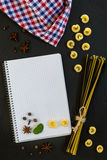 Blank cookbook with conventional and black uncooked Italian pasta Royalty Free Stock Photos