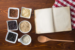 Blank cookbook and different rice varieties. Top view Stock Photos