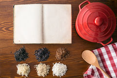 Blank cookbook and different rice varieties. Top view Royalty Free Stock Photo