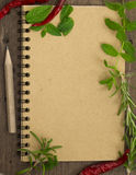 Blank cookbook for recipes. With fresh herbs and chili peppers Stock Images
