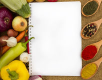 Blank cookbook for recipes. With fresh vegetables around it stock image