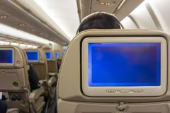 Blank copy space blue screens display on airplane seat monitors. On board airline flight of commercial aircraft royalty free stock image