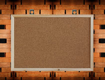 Blank cork board on wooden wall Royalty Free Stock Images