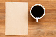 Blank cover book and cup of black coffee on brown wooden backgro. Top view of blank cover book and cup of black coffee on brown wooden background Royalty Free Stock Photography