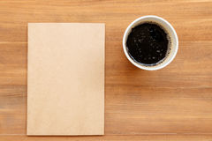 Blank cover book and cup of coffee on brown wooden background Royalty Free Stock Photos
