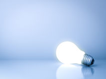 Blank creative idea background concept with one glowing idea light bulb on blue Royalty Free Stock Photography