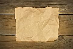 Blank crumbled brown paper on rustic wood Royalty Free Stock Photo