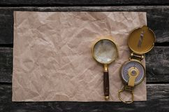 Crumpled paper page, compass and magnifying glass. Blank crumpled page with copy space for treasure map, compass and magnifying glass on old adventure table Royalty Free Stock Photo