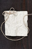Blank crumpled sheet of paper with rope bow Royalty Free Stock Photo