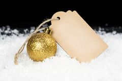 Blank decorative cardboard tag and golden glittering ornament si. Tting on snow, black background with space for text. Christmas, Sale or holiday concept stock photography