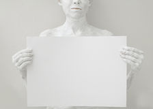 Blank design poster template. Woman covered with white paint holding a paper Stock Photo