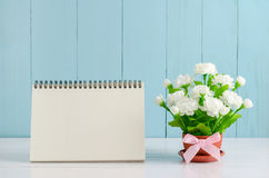 Blank desk calender with beautiful Jasmine flower. Blank desk calender card paper and beautiful Jasmine flower bouquet with pink ribbon bow on white and blue royalty free stock image