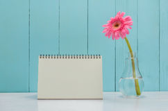 Blank desk calender with pink Gerbera daisy flower. In bulb glass vase on white and wooden background Stock Photography
