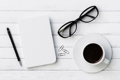 Blank diary, pen, cup of coffee, clips and glasses on white wood Stock Photos