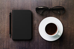 Blank diary, pen, cup of coffee and glasses on dark brown wooden Stock Image