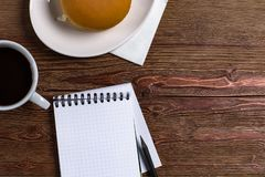 Blank diary with a pen on a wooden background with coffee and sandwich royalty free stock photo
