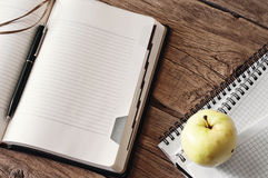 Blank diary on wooden table with apple closeup Royalty Free Stock Image