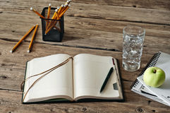 Blank diary on wooden table with a glass of water, apple and pencil closeup Royalty Free Stock Photos