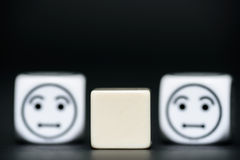 Blank dice with emoticon dice (confused) in background Stock Images