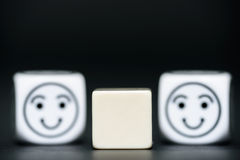 Blank dice with emoticon dice (happy) in background Stock Photography