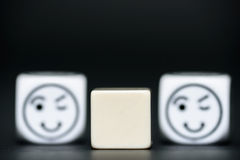 Blank dice with emoticon dice (happy, blinking) in background Stock Photos