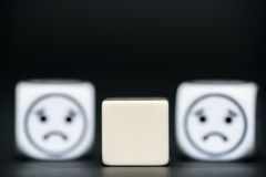 Blank dice with emoticon dice (sad) in background Royalty Free Stock Photos