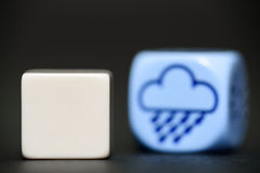 Blank dice with weather dice (rain) in background Stock Photography