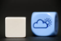 Blank dice with weather dice (sunshine) in background Stock Photo