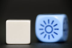 Blank dice with weather dice (sunshine) in background Royalty Free Stock Photography