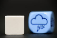 Blank dice with weather dice (thunderstorm) in background Royalty Free Stock Photography