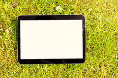 Blank digital tablet on green grass Royalty Free Stock Photo