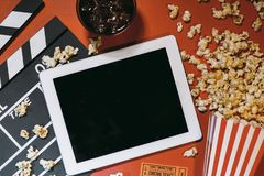 Blank digital tablet, popcorn, filmstrip, cinema and movie onlin. E streaming concept royalty free stock photography