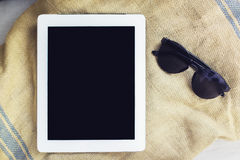 Blank digital tablet and sunglasses Royalty Free Stock Photo