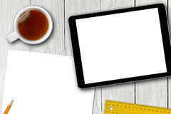 Blank digital tablet, tea cup and paper sheet on wooden table Royalty Free Stock Images