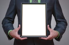 Blank diploma or certificate mockup. Blank diploma or certificate mock up in businessman hand. Empty photo frame border with copy space Royalty Free Stock Photography