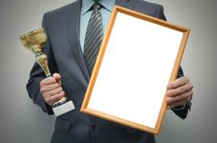 Blank diploma certificate mockup and golden award cup in the winner hands. Man is holding a blank diploma or certificate frame with copy space and golden award royalty free stock photo