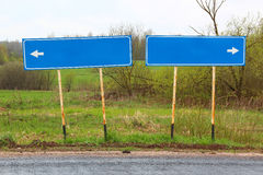 Blank direction blue signpost on the asphalt road on the background of green fields and bushes Royalty Free Stock Photo