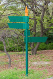 Blank direction green signpost in the park. Stock Photos