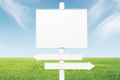 Blank direction signs on a background of green grass and blue sk. Y, mock up Stock Image