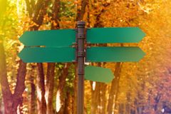 Blank directional road signs against autumn foliage. Green metal arrows on the signpost. stock images