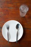 Blank dish, spoon and fork. On wood table Stock Photos