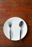 Blank dish, spoon and fork. On wood table Royalty Free Stock Image