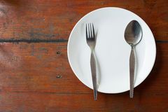 Blank dish, spoon and fork. On wood table Royalty Free Stock Photos
