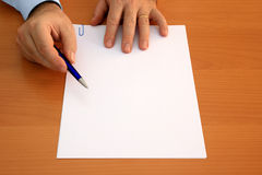 Blank document to sign. Male hands holding ballpoint pen pointing at blank document to sign Stock Image